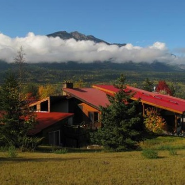 Family-style European inn with cloud-covered mountains in the background and blue sky above