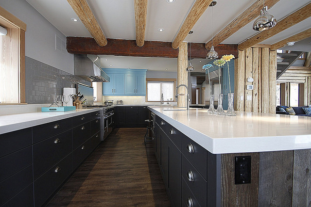 A combination of modern and rustic kitchen.  The lower cabinets are dark with white countertops.  The few upper cabinets are in aqua blue.  Ceiling beams are old reused barn wood.
