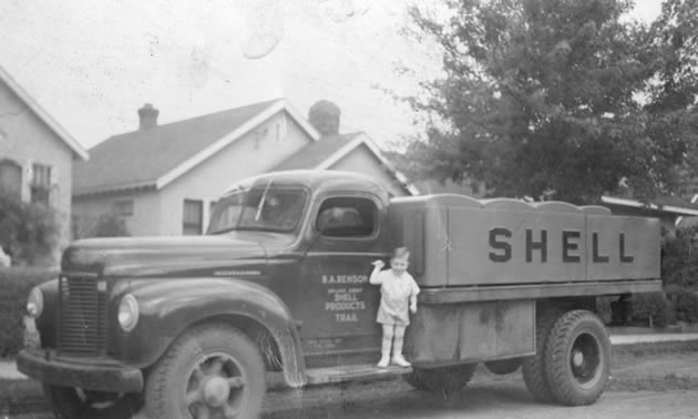 A black and white photo of a young boy standing on the side of an old fuel truck.