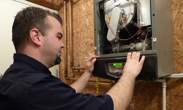 A man examining a heating system.