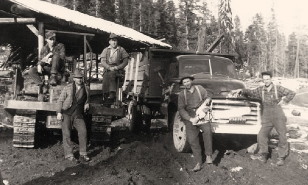 A black and white photo of a logging crew at camp.