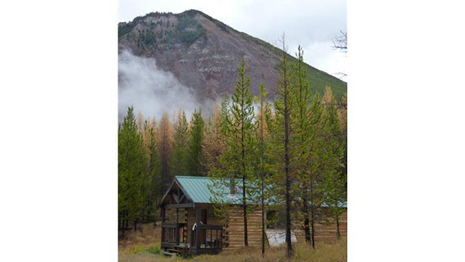 Log cabin in a wilderness setting with trees and mountains