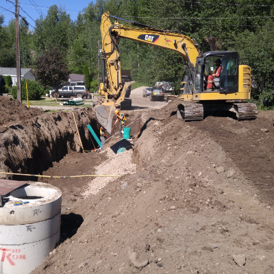 An excavator digs a deep trench where a road used to be.