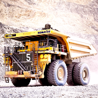 A large Komatsu dump truck works in a quarry
