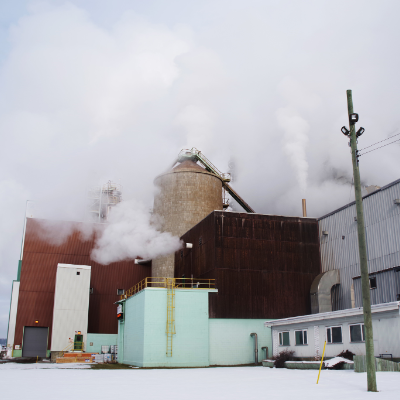 An exterior aspect of the process shows the unbleached pulp storage tower (centre), along with the maintenance, power and recovery, and pulping process offices (lower right). Excess thermal energy is released to the environment in the form of steam energy.
