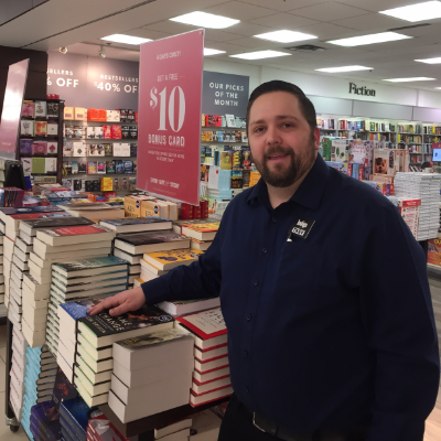 Tasy Strouzas stands inside Cole's Bookstore next to a collection of books