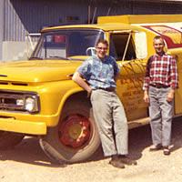 Two men standing beside a fuel truck.