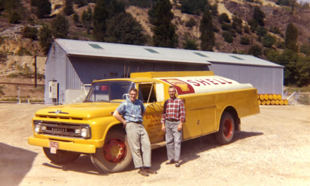 An old photo of two men standing beside a yellow fuel truck.
