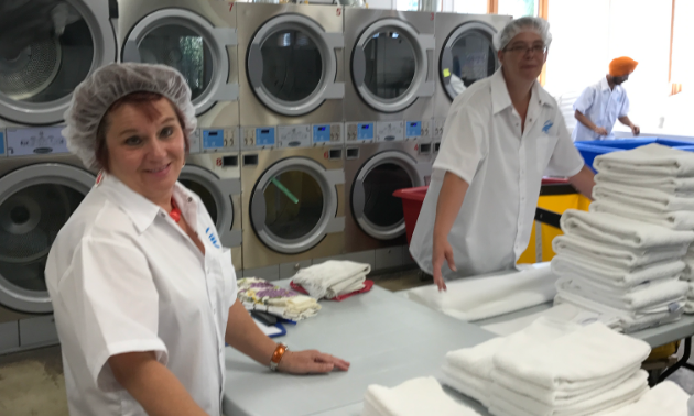 JJ's Laundry Depot workers smile while washing laundry