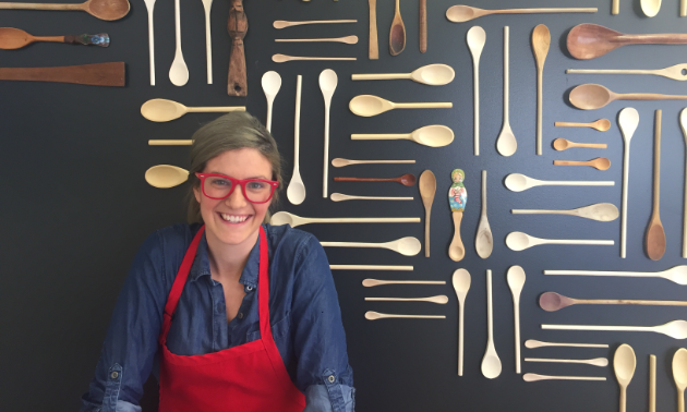Kayla Sebastian stands in front of a wall of wooden spoons