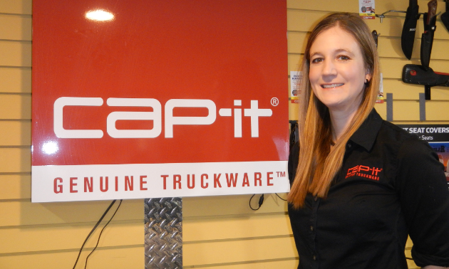 Nicole Kauffman poses next to a Cap-it sign