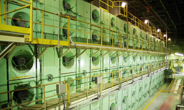 The pulp sheet dryer is shown. The pulp sheet discharged from the third press nip undergoes 27 passes in the Flakt dryer. The Flakt dryer increases the sheet consistency from approximately 46 per cent (containing 54 per cent water) to 90 per cent air dry content (containing 10 per cent water). Residual water in the pulp sheets ensures integrity and prevents cracking due to dryness.