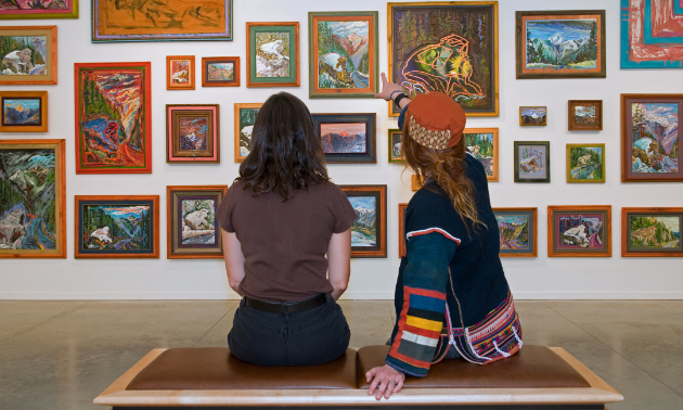 Picture of two people looking at paintings in an art gallery.