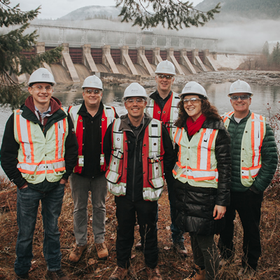 Hard-hatted representatives of Austin Engineering, FortisBC and Selkirk College are gathered at the Corra Lin dam