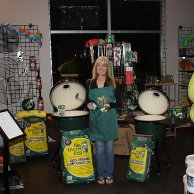 Margeaux Bauman, co-owner of Kootenay Valley Water & Spas, is standing with the Big Green Egg barbecue and a big bag of natural charcoal.