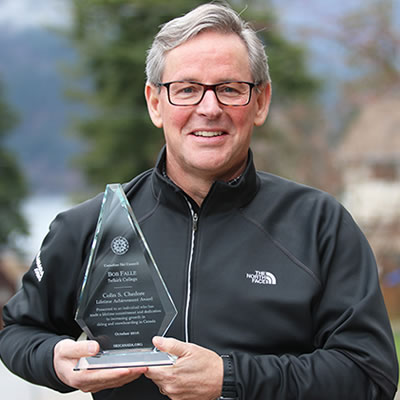 Picture of Bob Falle holding the Lifetime Achievement Award from the Canadian Ski Council.