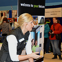 A woman representing Lethbridge College interacts with two attendees at the College of the Rockies Career and Job Fair.