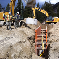 Earth moving equipment, a trench holding a metal framework, and a few workers