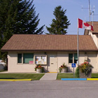 Small house attached to two-bay firehall, with Canada flag flying out front