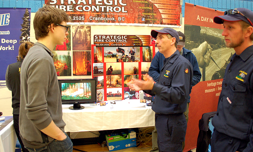 A man in a grey shirt talks to a recruiter who wears his navy fire gear and a ball cap. Behind them is an orange display and photos promoting Strategic Fire Control.