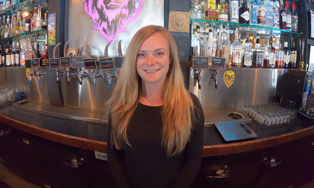 Carly Hadfield stands before the bar at the Lion's Head Smoke & Brew Pub in Castlegar, B.C., where she is the co-owner and vice-president