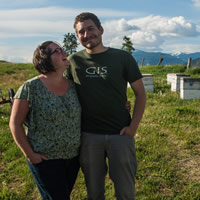 Jen smiles and looks up at Joel who grins at the camera. Behind them is a green field, mountains and white hive boxes.
