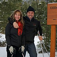A woman and man wearing snowshoes stand beside a sign saying Cedar House Trail Head
