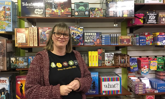 Dee Connell of Main Street Fun & Games, stands before shelves full of games and toys