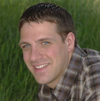 A head shot of Dylan Zorn wearing a brown plaid shirt against a field of green.