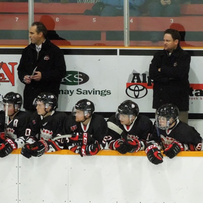 Kimberley Dynamiters head coach Derek Stuart stands with two other coaches behind the bench at a Kimberley Dynamiters hockey game