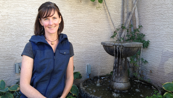 Tammy Bessant sits near a water fountain in front of her house in Cranbrook from which she runs her business, EarthWear.