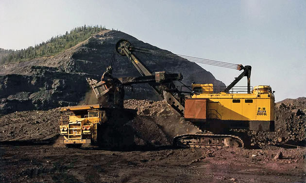 A yellow Teck truck shovel in front of a large coal pile