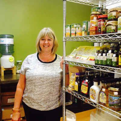 Co-owner Leanna Spring of From the Ground Up in Cranbrook stands next to a shelf full of health foods.