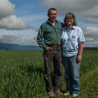 Roy and Sherry stand with their arms around each other beside a dirt road. Beside them is a green field and a blue sky with puffy clouds.