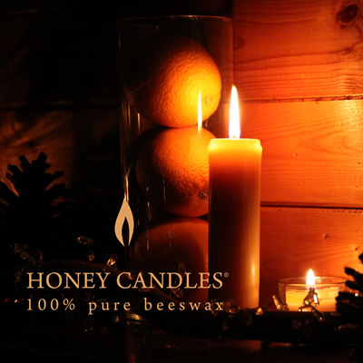 Several beeswax candles are burning with a soft golden glow. These candles are from Honey Candles near Kaslo, B.C.