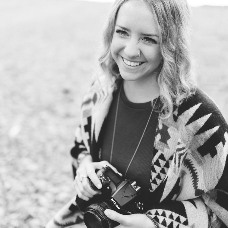Jacey Paton in a field, smiling with her camera
