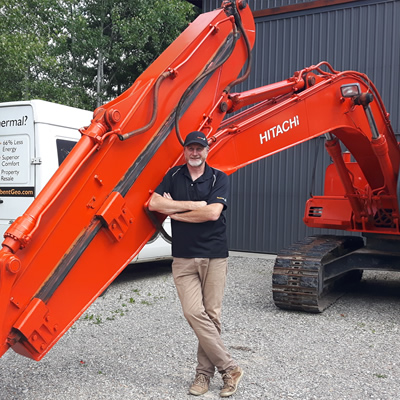 John Managh, co-owner of Hellbent Geothermal, stands in front of a large piece of machinery.