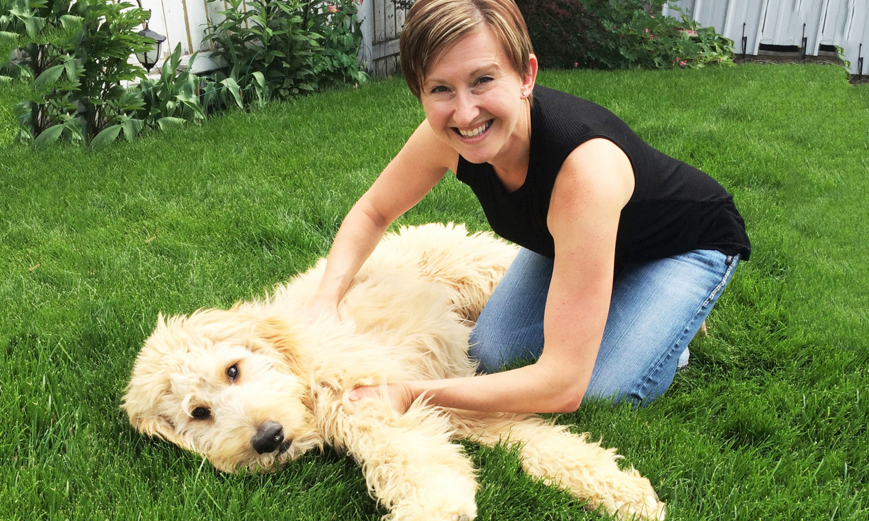 Joanna Sleik playing with Buddy, her adorable golden doodle dog