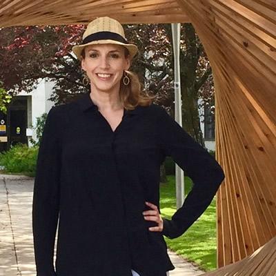 "Joy Barrett, cultural development officer for Nelson, B.C., and executive director of Castlegar Sculpturewalk, stands within ""Sculpture Walk"" by Spring Shine, Christopher Petersen and Hans Winter (2016)."