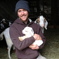 Caley (Left), Torin and Andrew Bennett this past winter with goat barn and market gardens in background