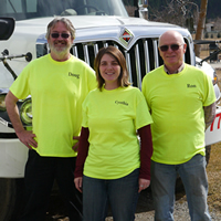 Cynthia Howard, manager of Kettle Valley Waste, stands with owner Ron Liddle and a driver. They all wear bright yellow company shirts.