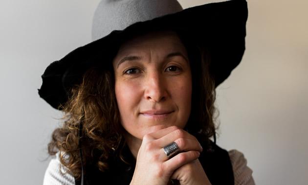 Kat Cadegan, jewelry designer, poses wearing a wide-brimmed hat