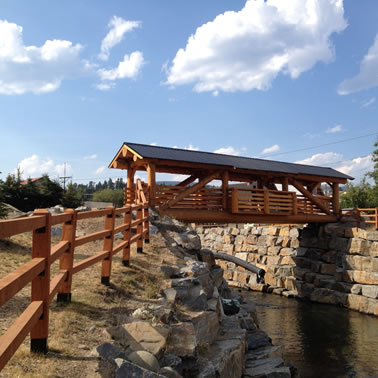 A pedestrian, timber-frame wooden bridge with a metal roof spans Mark Creek in Kimberley, B.C.