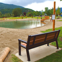 A bench overlooking the bottom pond and water slides at the Millennium Park Natural Outdoor Swimming Ponds project in Castlegar, B.C.