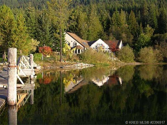 Home near Nelson reflecting in the water of Kootenay Lake.