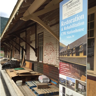 Picture showing a run-down railway station with a sign detailing the restoration project the building is undergoing.