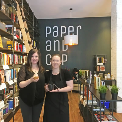 Brandi O'Neill (L), owner, and one of her staff stand next to a tall shelf of books.