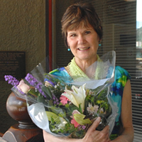 Patty Axenroth stands with a bouquet and a certificate naming her a winner in the West Kootenay Influential Women in Business Awards.
