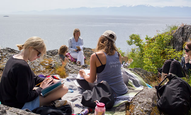 Workshop participants are sitting on a rocky area overlooking the ocean on B.C.'s coastline.