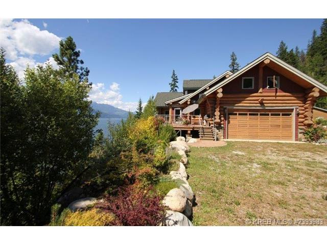 A view of the outside of the log home, sitting on a hill overlooking Kootenay Lake.